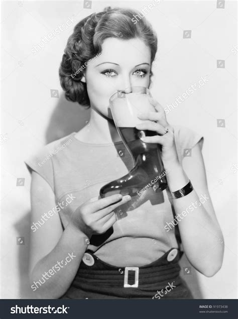 Woman Drinking Beer Out Of A Boot Shaped Glass Stock Photo